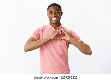 Wais-up shot of sincere kind and cute african american young male sharing love and tender feelings showing heart gesture and smiling broadly confessing in sympathy to mother over white wall