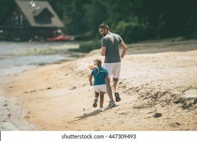 Wait for me daddy! Full length rear view of cheerful father and daughter jogging at the riverbank together