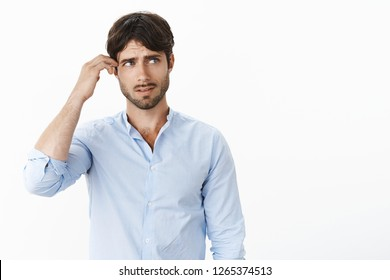 Wait a sec let me think. Confused guy in stupor scratching head looking at upper right corner clueless and questioned as trying to understand or find solution posing unaware over gray background