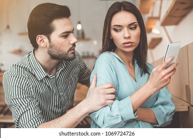 Wait. Worried young man is consoling his girlfriend while touching her arm gently. Woman is holding mobile phone and looking at boyfriend with offence