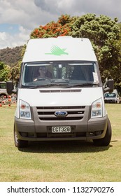 WAITANGI, NEW ZEALAND – JANUARY 2, 2009: Front view of campervan with driver on a meadow in Waitangi, New Zealand.