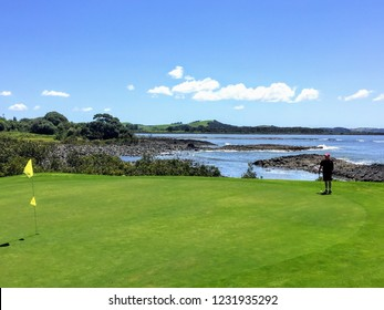 Waitangi, North Island, New Zealand - February 19th, 2016: A man lining up a putt while golfing in Waitangi, North Island, New Zealand along the shores of the tourist oasis the Bay of Islands.