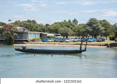 Waitangi, North Island, New Zealand-December 18,2016: Double hulled old war style canoe moored to the waterfront with people swimming in the bay in Waitangi, New Zealand