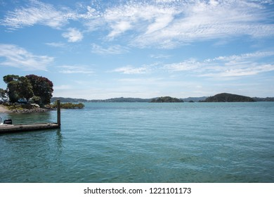 Waitangi, North Island, New Zealand-December 18,2016: Motorboat at do​ck with scenic Tasman Sea water and green landscape in Waitangi, New Zealand