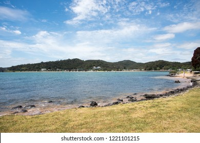 Waitangi, North Island, New Zealand-December 18,2016: People walking on re​mote beach with the Tasman Sea waters and stunning rolling, green landscape in Waitangi, New Zealand