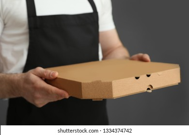 Waiter in apron with pizza box on grey background, closeup. Food delivery service