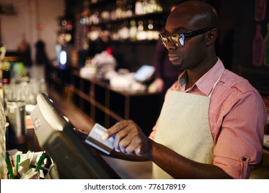 Waiter in apron standing by cash-desk in front of monitor and passing payment of customer or entering data about new order