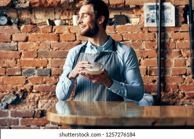 A waiter in an apron writes something in a notebook and looks away