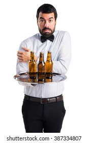Waiter with beer bottles on the tray freezing