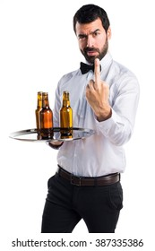 Waiter with beer bottles on the tray making horn gesture