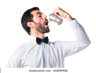 Waiter with beer bottles on the tray holding a coffee pot