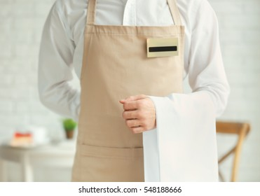 Waiter in beige apron with towel in a cafe, close up