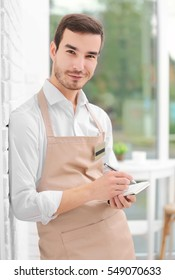 Waiter in beige apron writing down an order in a cafe