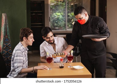 waiter with biosecurity measures in times of coronavirus. person serving sushi in a reopened restaurant