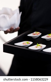 waiter bring  canapes on tray to guest