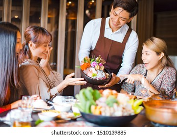waiter  bring  seafood  and serving group of friends in restaurant.