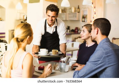 Waiter is bringing drinking and delicious desserts to clients of cafe.