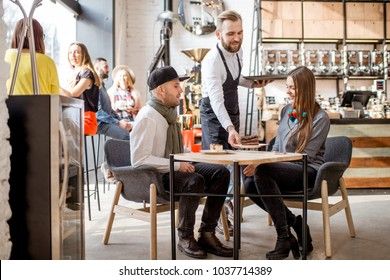 Waiter bringing a sweet dessert to a young couple sitting together in the cafe