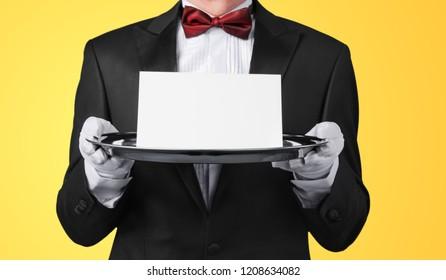 Waiter or butler wearing a tuxedo holding