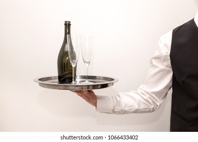 A waiter / butler in white shirt and black suit vest carrying an silver tray with a bottle of champagne and two glasses. White background.