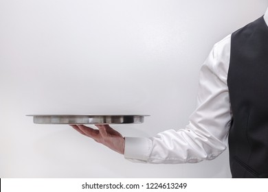 A waiter / butler in white shirt and black suit vest carrying an empty silver tray. Copy space on white background.