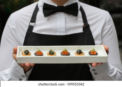 waiter with canapes / canapes with caviar / catering