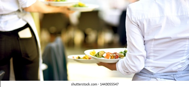 Waiter carries food at work