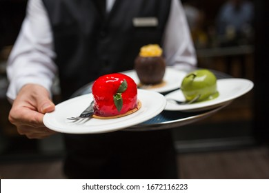 Waiter carries a tray with fruit shaped desserts. Fine dining sweet food in restaurant. Strawberry, coconut and apple shaped glazed cake. Depth of field.