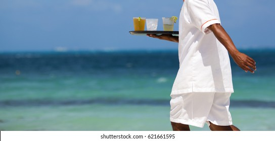 Waiter carrying cold drinks on the beach. Turquoise sea in the background. Waiter dressed in white clothes. Focus point on the drinks.