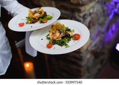 Waiter carrying a plate with fish and salad on a wedding