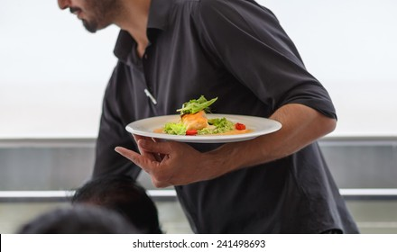 Waiter carrying a plate with salad dish on a wedding. Celebration event, serving food for the guests.