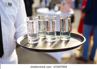Waiter carrying a tray with wine glasses, orange juice and miniral water on an outdoors reception