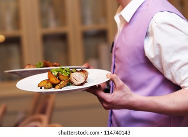 Waiter carrying two plate with meat and baked potato