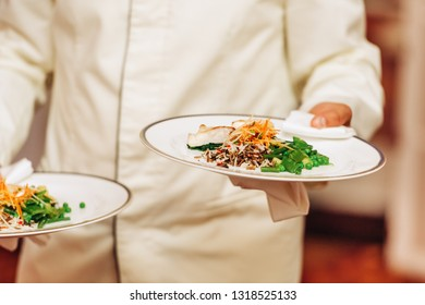 Waiter carrying two plates with fish and rice dish on some festive event, party, wedding reception or catered event