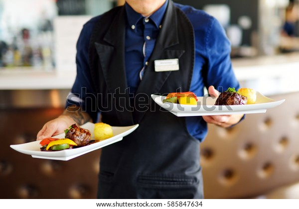 Waiter carrying two plates with meat dish on some festive event, party, wedding reception or catered event