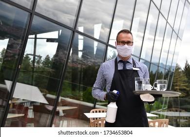 Kellner, der den Tisch mit desinfizierendem Spray in einem Restaurant mit Schutzmaske reinigt, Handschuhe mit neuem Normalkonzept