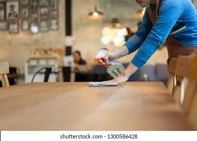 Waiter cleaning the table with spray disinfectant on table in restaurant.