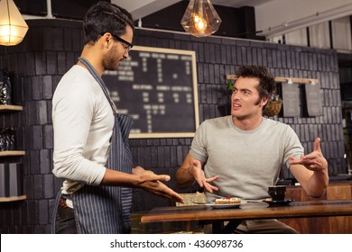 Waiter and customer having a discussion in a coffee shop