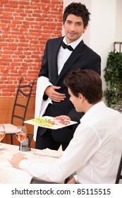 Waiter deliver in meal in restaurant