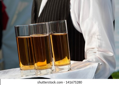 Waiter with dish of juice glasses