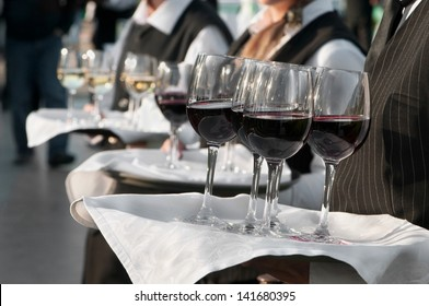 Waiter with dish of wine glasses