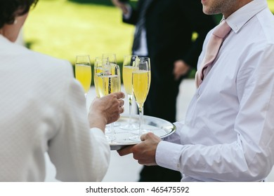 Waiter dressed in white carries glasses with champagne