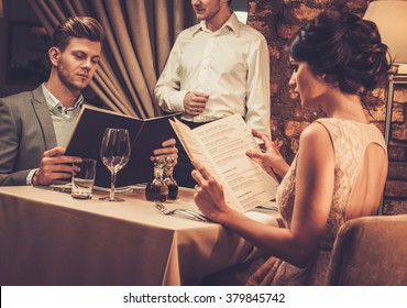 Waiter explaining the menu to stylish wealthy couple in restaurant.