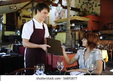 waiter giving menu to female costumer at the restaurant