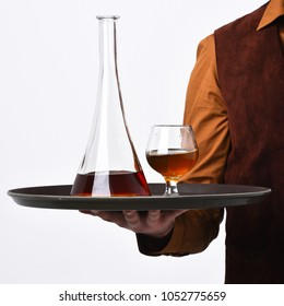 Waiter with glass and bottle of whiskey on tray. Restaurant beverages concept. Males hand holds cognac on white background. Barman in vintage suede leather waistcoat serves scotch or brandy.