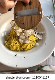 Waiter is grating black truffle on freshly made pasta in Italian restaurant