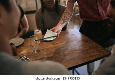 Waiter handing a customer the bill for dinner and drinks after a night out with friends at a bar