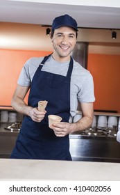 Waiter Holding Cup And Cone At Ice Cream Parlor