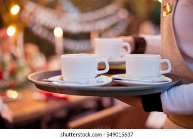 waiter holding cups on tray