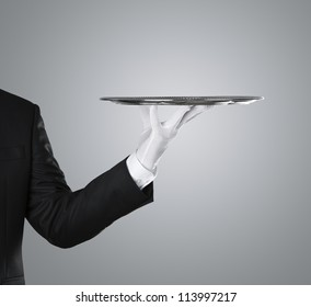 Waiter holding empty silver tray over gray background with copy space